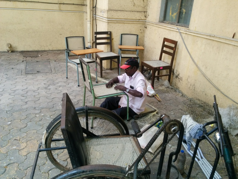 Figure 10: Krishna, a physically handicapped man is hired by TISS to repair broken chairs. In most public institutions, one finds broken, damaged furniture, equipment (such as computers, projectors etc) lying around in neglected heaps in some corner since no one bothers to get it repaired. However, while TISS is itself a public institution, this is rarely (or never) the case. As we see in this picture, damaged furniture is not only immediately repaired but is repaired by a physically handicapped person so that he can earn his livelihood while providing an extremely essential service to the institution.